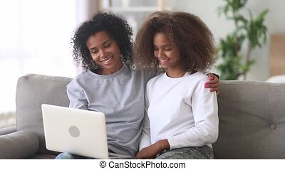 Mixed race mother daughter watching movie on laptop at home...