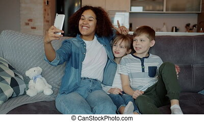 Mixed race nanny taking selfie with little kids brother and sister with smartphone camera