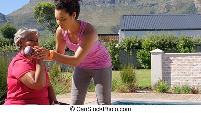 Mixed-race personal trainer assisting asian senior woman in exercising at backyard of their home 4k