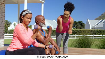 Mixed-race personal trainer assisting senior black couple in exercising at backyard of their home 4k