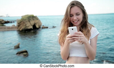 Mixed race pretty smiling young woman holding and looking at smart phone on hawaiian beach in sunset