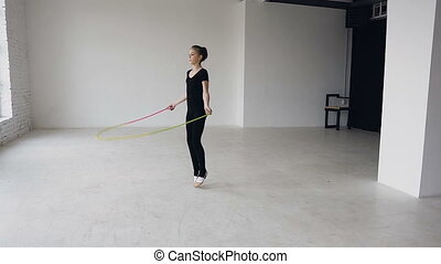 Mixed race. Skipping girl training at the gymnastics school working out is healthy fitness. Healthy teenage girl skipping with a jump rope. Sporting exercise, stretch, flexibility, aerobics