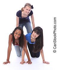 Mixed race teenage girl friends in fun pyramid