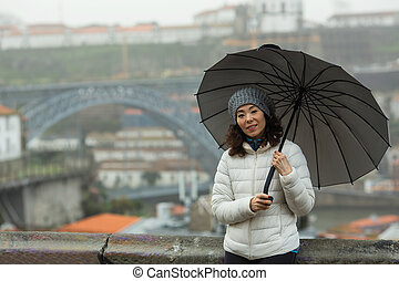 Mixed-race tourist woman with an umbrella in foggy weather on the background of the Dom Luis I Bridge in Porto, Portugal.