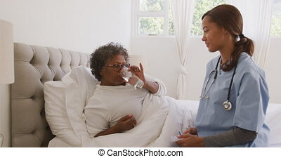 Mixed race woman being visited at home by a mixed race nurse, drinking water, social distancing and self isolation in quarantine lockdown, in slow motion