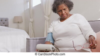 Mixed race woman checking her blood pressure. Social distancing and self isolation in quarantine