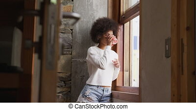 Mixed race woman drinking coffee - Front view of a young ...