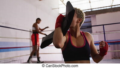 Front view close up of a mixed race female boxer with short curly hair and wrapped hands, celebrating and kissing the victors belt after beating her opponent in a boxing match, the opponent is standing against the ropes on the other side of the ring, slow motion