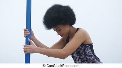 Mixed race woman holding bar - Side view of mixed race woman...
