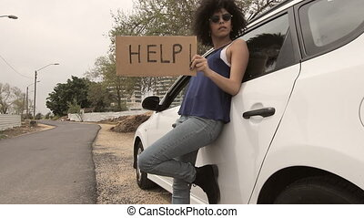 Mixed race woman lean on car with help sign - Mixed race...