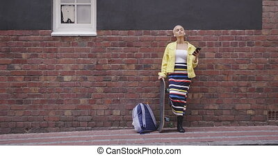 Mixed race woman leaning against a brick wall with her ...