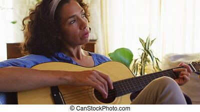 Mixed race woman playing guitar and singing while sitting on the couch at home