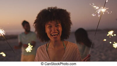 Mixed race woman playing with fire on the beach - Mixed race...