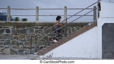 Side view of two mixed race women enjoying free time by the seaside, running up the stairs, in slow motion