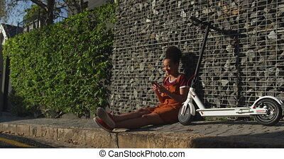 Mixed race woman sitting on sidewalk - Side view of mixed ...