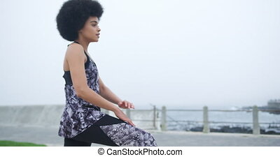 Mixed race woman stretching on docks - Side view of mixed ...