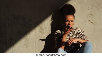 Front view of mixed race woman enjoying free time in an urban park on a sunny day, talking on the phone, sitting by a wall, slow motion