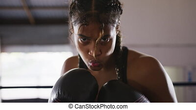 Mixed race woman using boxing gloves - Portrait close up of ...