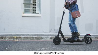 Mixed race woman using electric scooter - Side view low ...