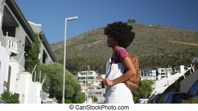 Mixed race woman walking on street - Low angle side view of ...