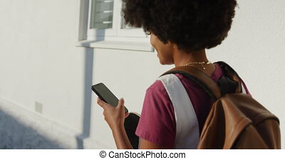 Over the shoulder view of mixed race woman enjoying free time on a street on a sunny day, walking, using the phone, slow motion, slow motion