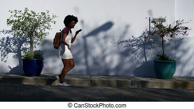 Mixed race woman walking on street - Side view of mixed race...
