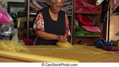 Mixed race woman working at a hat factory - Mixed race woman...