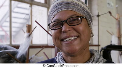 Mixed race woman working at a hat factory - Portrait close ...