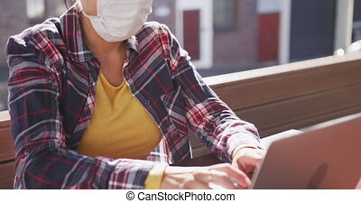 Side view of a mixed race woman with long dark hair sitting at a table in a cafe during the day, wearing a face mask against air pollution and coronavirus, working on a laptop computer in a cafe with buildings in the background in slow motion.