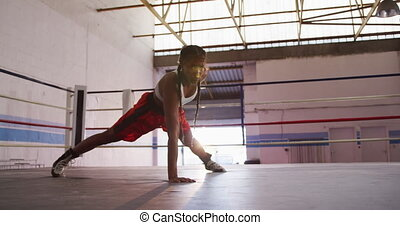Mixed race woman working out in boxing gym - Side view of a ...