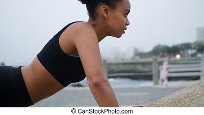 Mixed race woman working out on docks - Side view of mixed ...