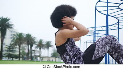 Side view of mixed race woman enjoying free time by the seaside, doing sit ups on the docks, in slow motion
