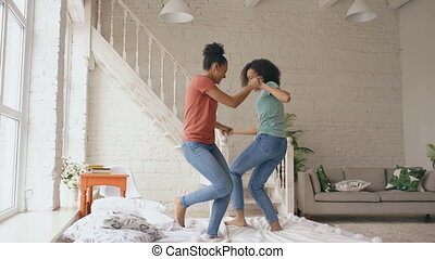 Mixed race young beautiful girls dancing on a bed together having fun leisure in bedroom at home