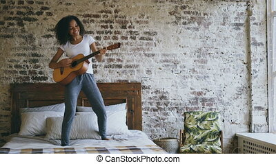 Mixed race young funny girl singing and playing acoustic...