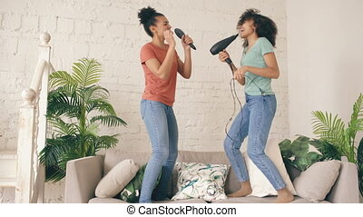 Mixed race young funny girls dance singing with hairdryer and comb jumping on sofa. Sisters having fun leisure in living room at home concept