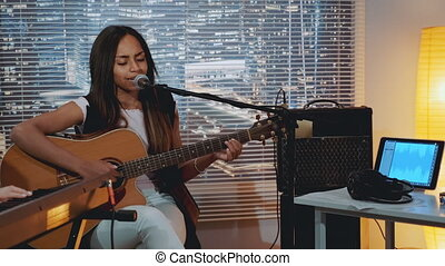 Mixed-race young lady playing guitar and singing into microphone during band rehearsal in home studio