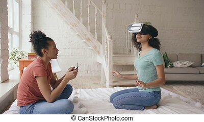 Mixed raced woman using virtual reality glasses while her friend holding digital tablet computer. Girlfriends play video game 3d technology concept at home