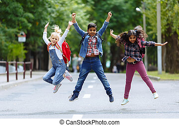 Mixed Racial Group happy children jumping in the park near school. Primary education concept.