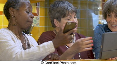 Mixed racial group of friends over 60 sharing tablet and...