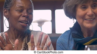 Mixed racial group of older women talking and smiling with drinks