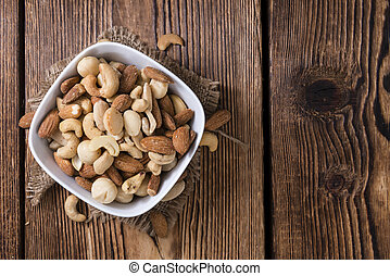 Mixed roasted and salted nuts (selective focus) on an old ...