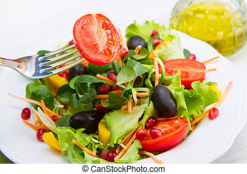 mixed salad with tomatoes in white plate on wood table