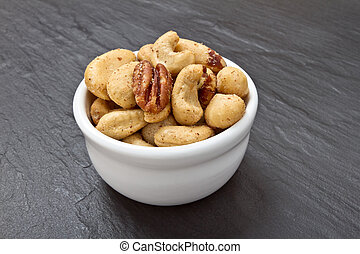 Mixed Salted Nuts in bowl on dark grey slate background.