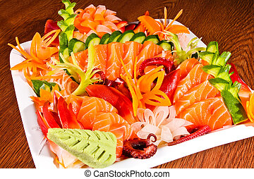 Mixed sashimi in white plate on wood table
