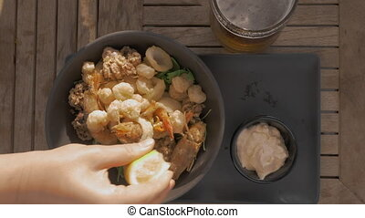 Top close-up view of pouring mixed seafood tempura dish with lemon juice. Meal served with sauce and glass of beer