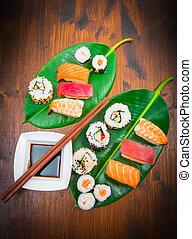 mixed sushi on green leaf