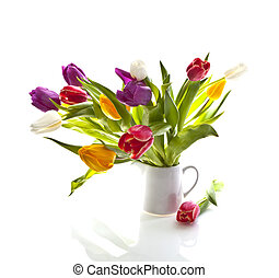 Mixed tulips in a jug on white background