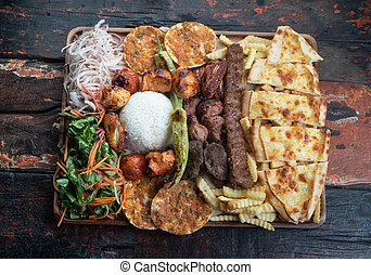 Mixed turkish kebab plate on rustic wooden table