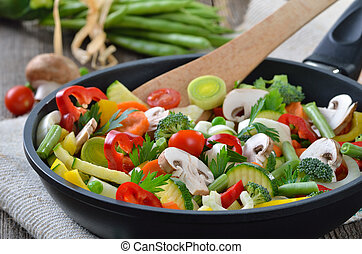 Chopped fresh vegetables in a skillet, ingredients in the background