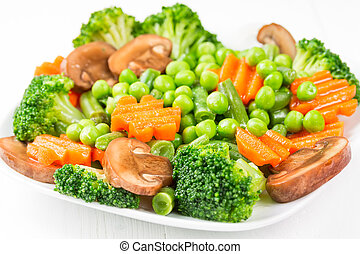 Mixed cooked vegetables on a white plate